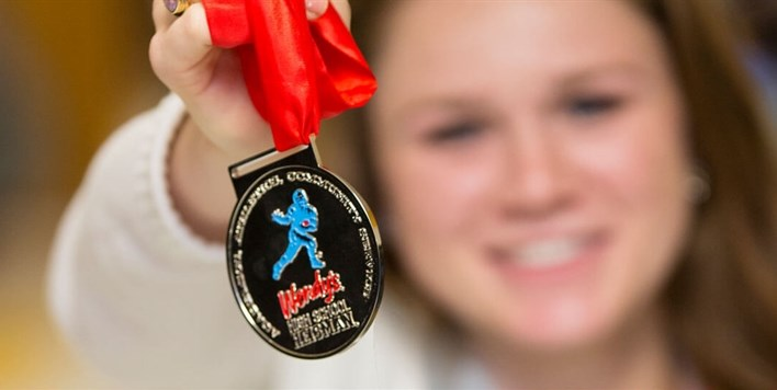 A smiling young lady holds a Wendy's High School Heisman medallion out in front of her.