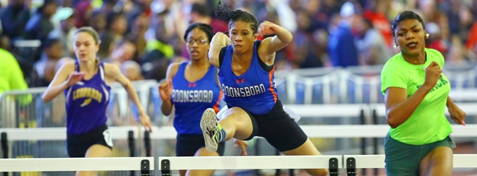 Female hurdlers race against each other at the 2017 Class 2A & 1A Indoor Track State Championships.