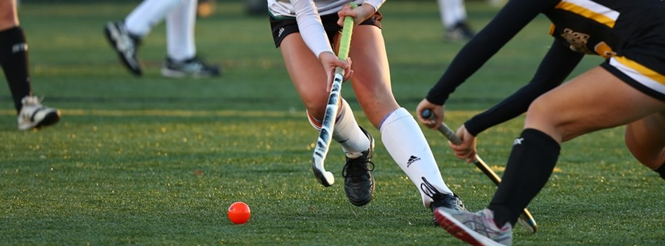 A Patuxent player dodges a South Carroll player in the 2018 Class 1A State Field Hockey Final.