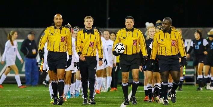 Four male soccer officials lead two girls teams onto the field at the State Finals pregame ceremony.